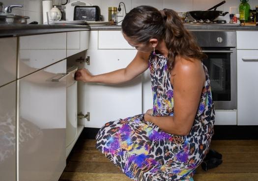 Vrouw schakelt de boiler in de keuken aan en uit