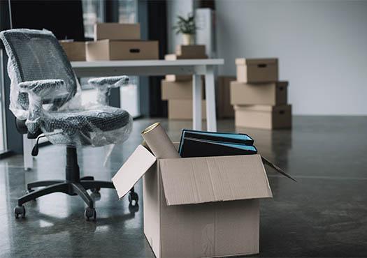 Leeg kantoor met een bureaustoel en kartonnen dozen